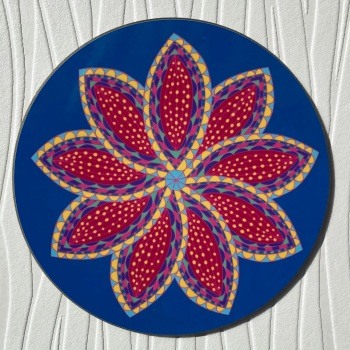 Circular blue coaster with stylised flower decoration