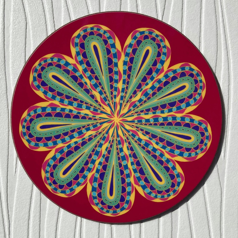 Circular red coaster with stylised flower decoration