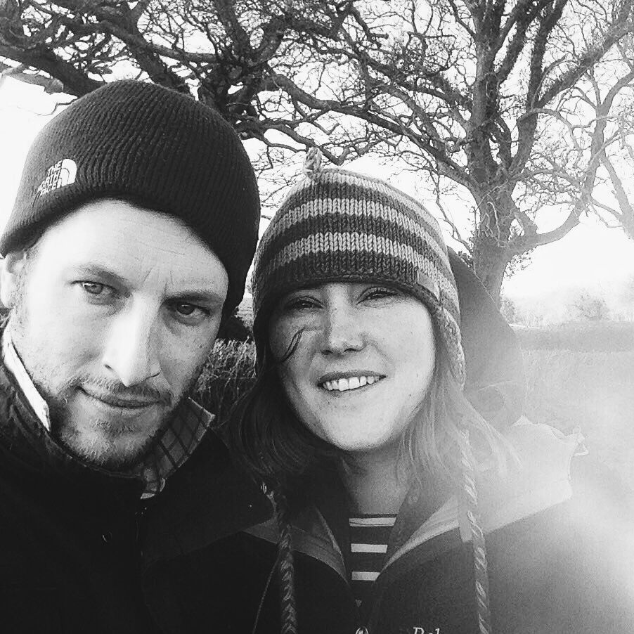 Black and white photo Ben and Nic outdoors wearing hats