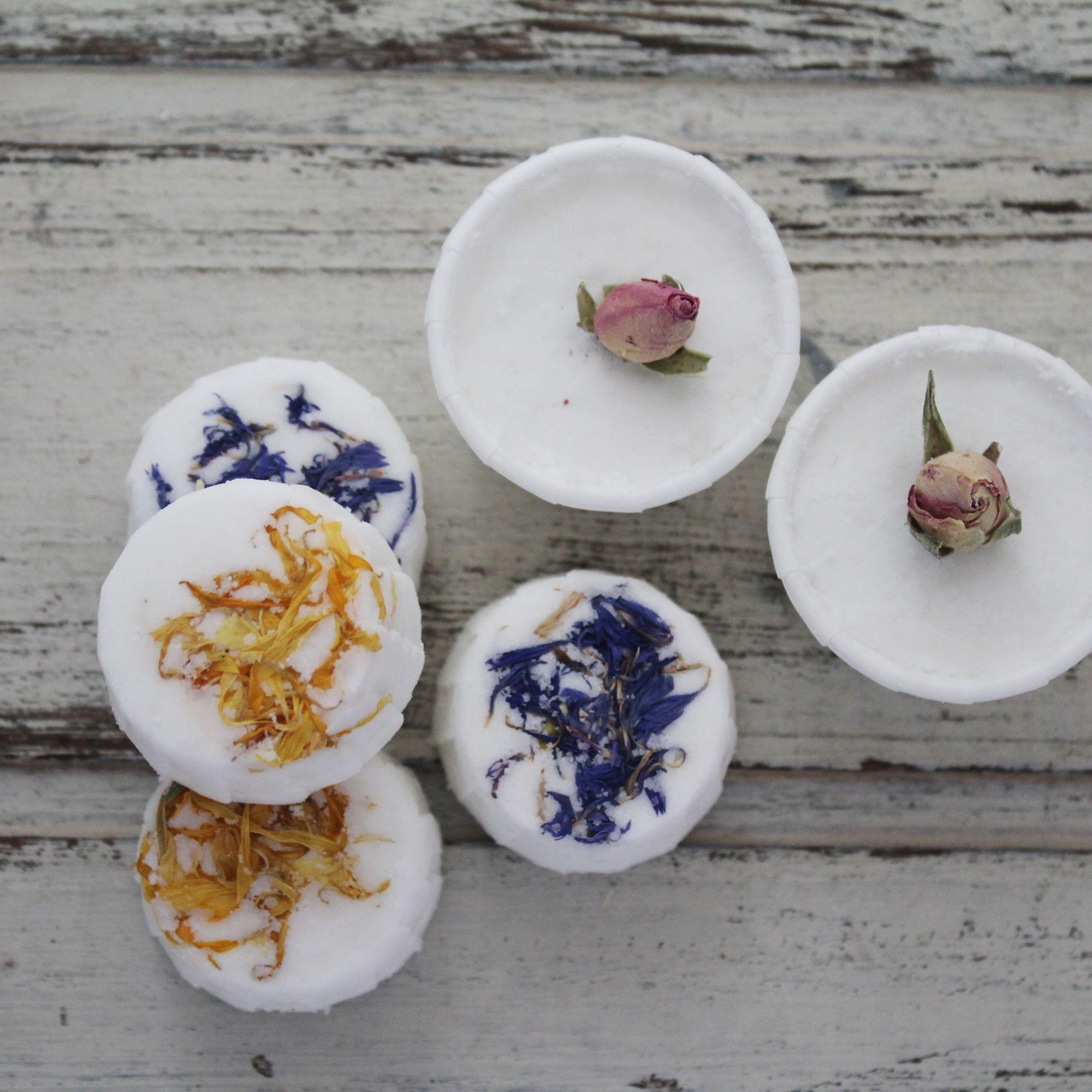 Flower topped round bath truffles on whitewashed wood