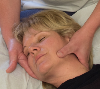 Cranial osteopathy being performed on a lady