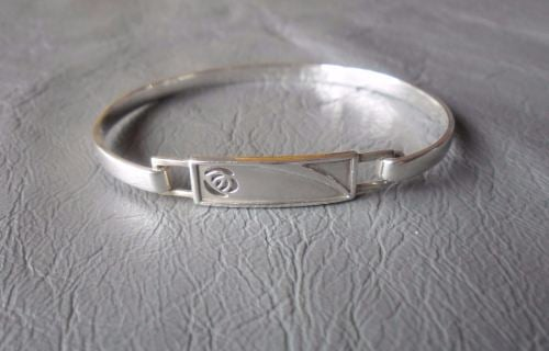 Sterling silver bangle with a cut-out rose panel