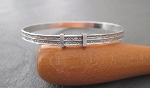 Vintage sterling silver Christening bangle; feathered leaf scroll