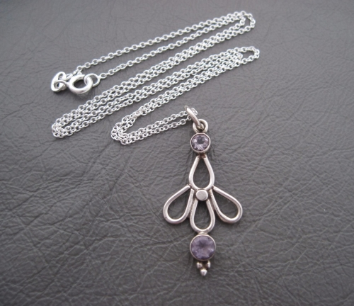 Sterling silver necklace; floral looped pendant set with amethyst