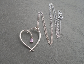 Elegant sterling silver heart necklace with pink stone detail