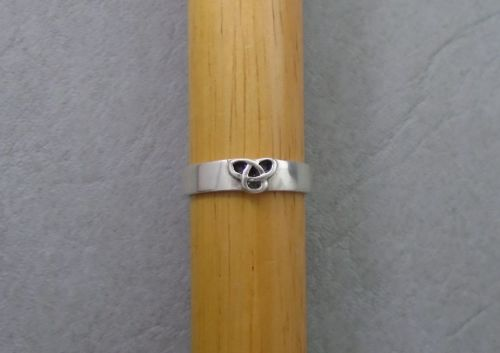 Sterling silver band ring with a small celtic knot