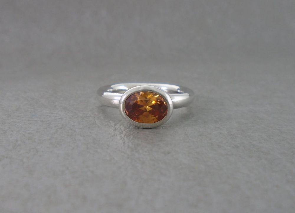 Solid sterling silver solitaire ring with a faceted orange stone