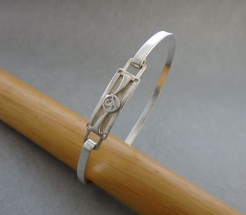 Sterling silver bangle with a small fancy panel