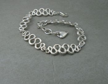Sterling silver bracelet with smooth wavy panels & heart tag