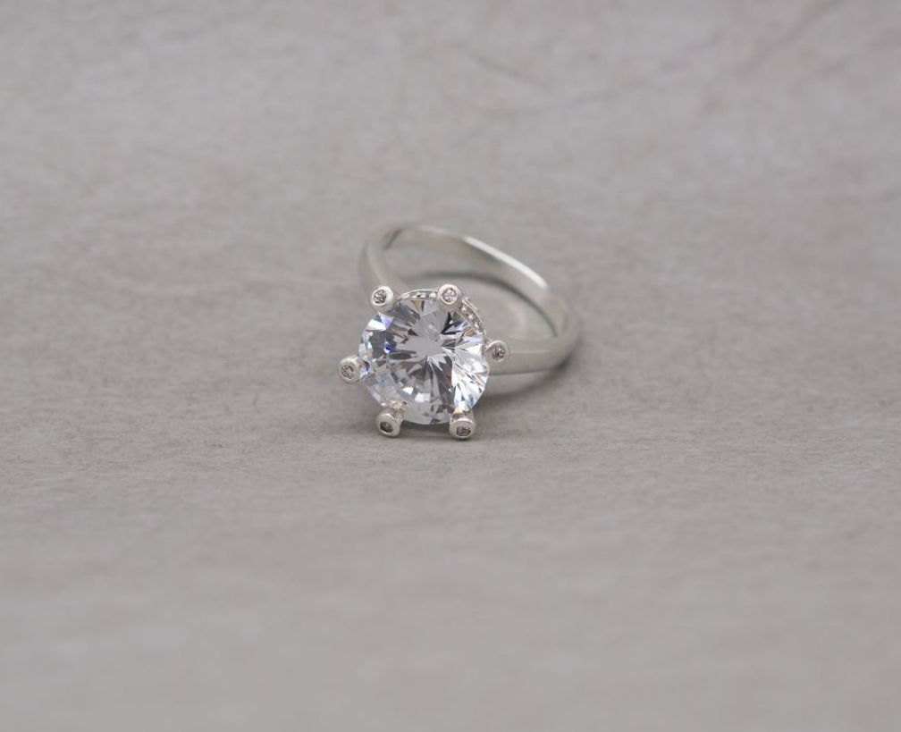 Substantial sterling silver & clear stone solitaire ring with accents