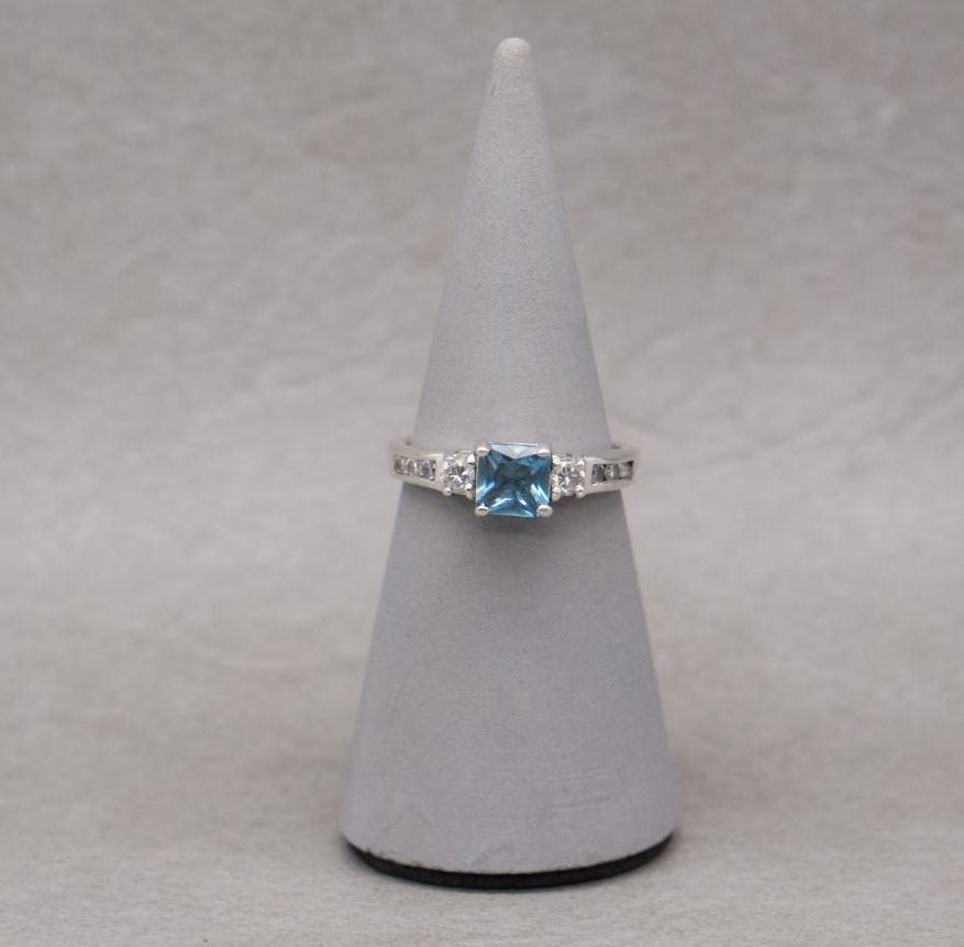 Sterling silver ring with a square blue stone and stepped accented shoulder