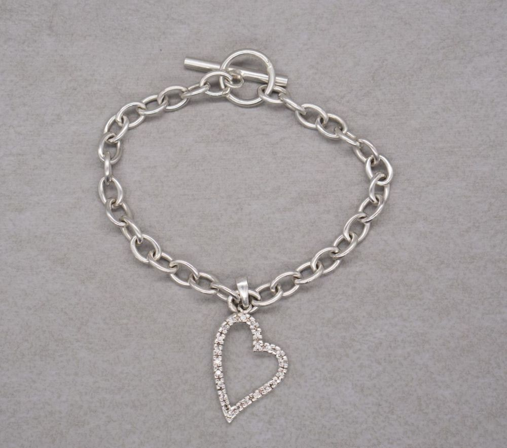 Sterling silver trace chain toggle bracelet with a clear stone heart charm