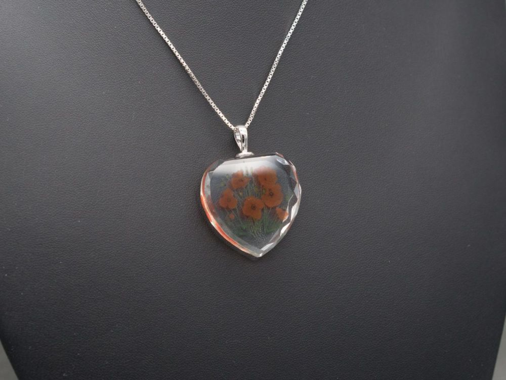 Sterling silver necklace with a faceted crystal heart pendant, poppy flower
