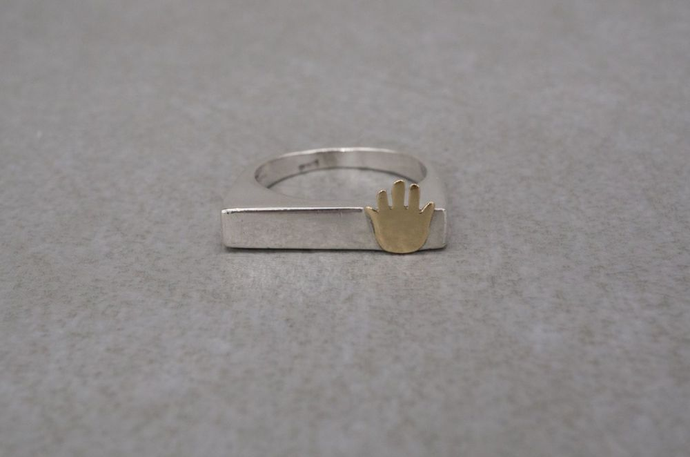 Unusual sterling silver ring with a golden hand