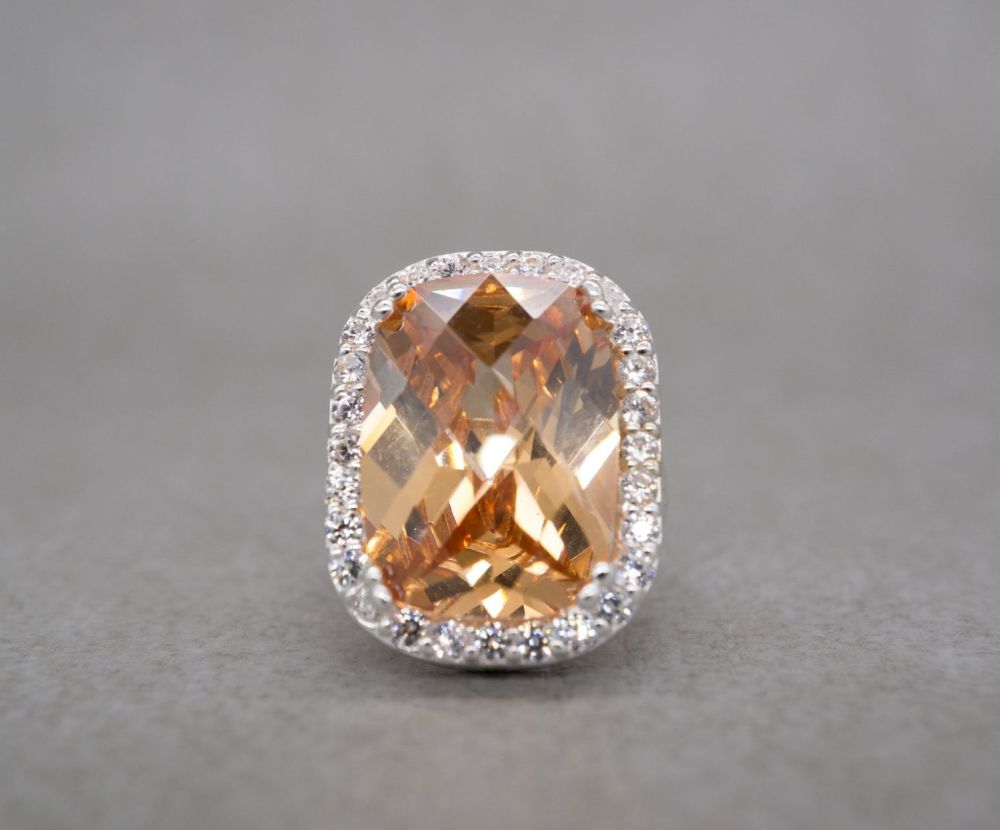 Sterling silver cocktail ring with a faceted orange cushion in a clear ston