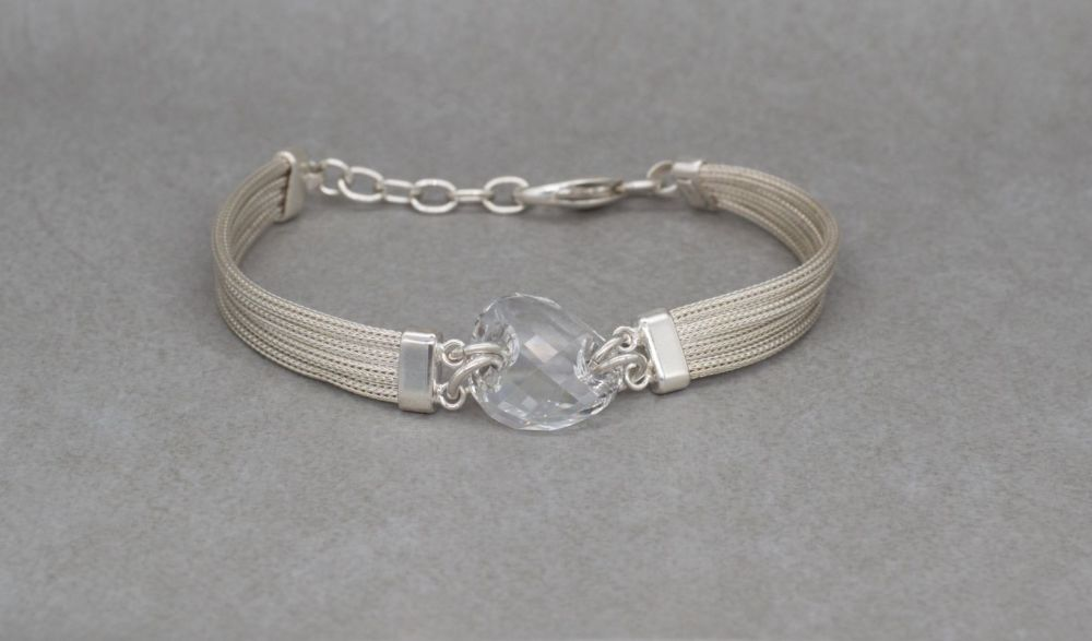 Sterling silver multi-chain bracelet with a faceted clear crystal