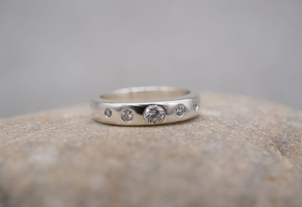Sterling silver ring with 5 flush-set graduated clear stones
