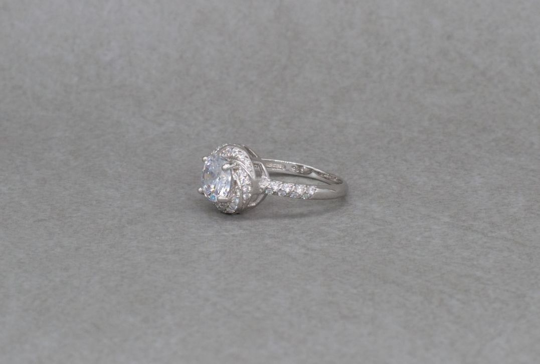 Sterling silver swirl mounted solitaire ring with accents