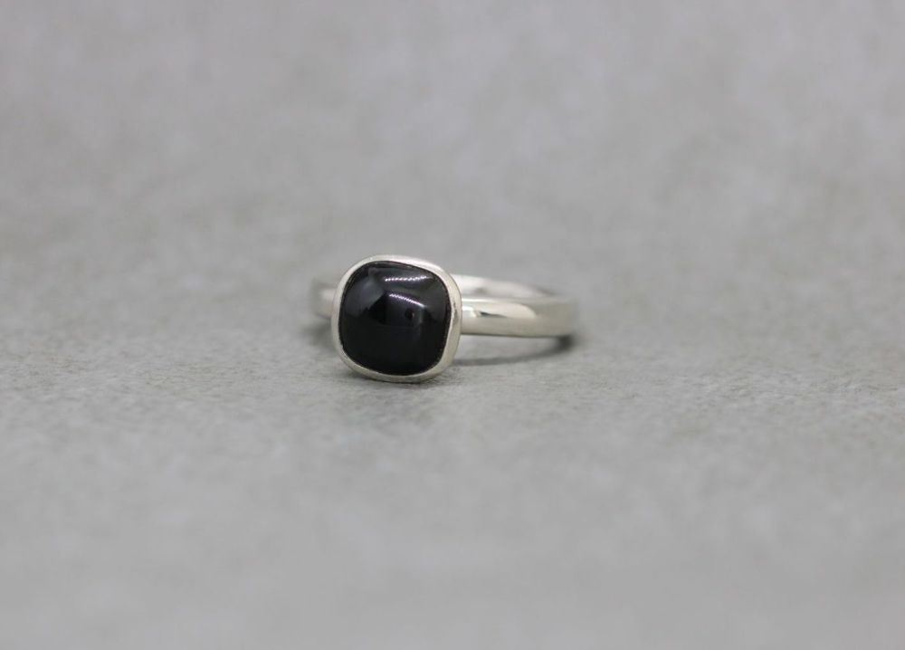 Proud sterling silver solitaire ring with a polished black stone