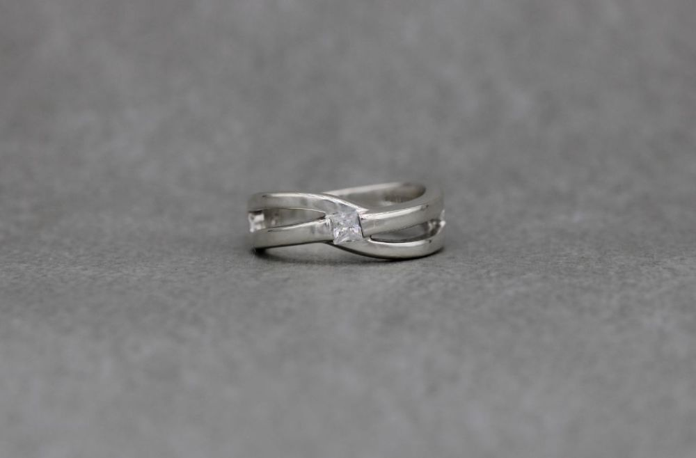 Sterling silver cross-over ring set with a single square stone