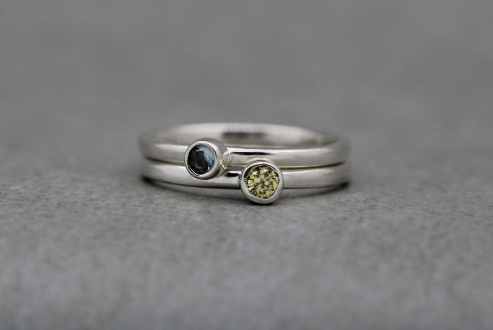A pair of sterling silver stacking rings with blue & lemon stones