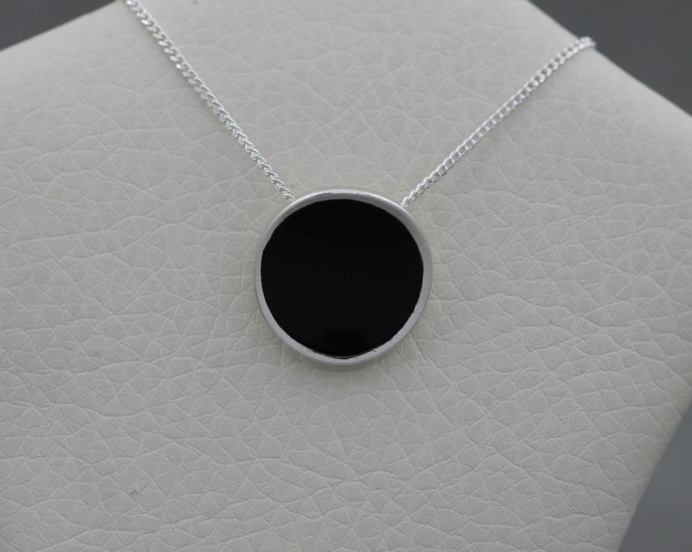 Sterling silver necklace with a small curved black onyx disc