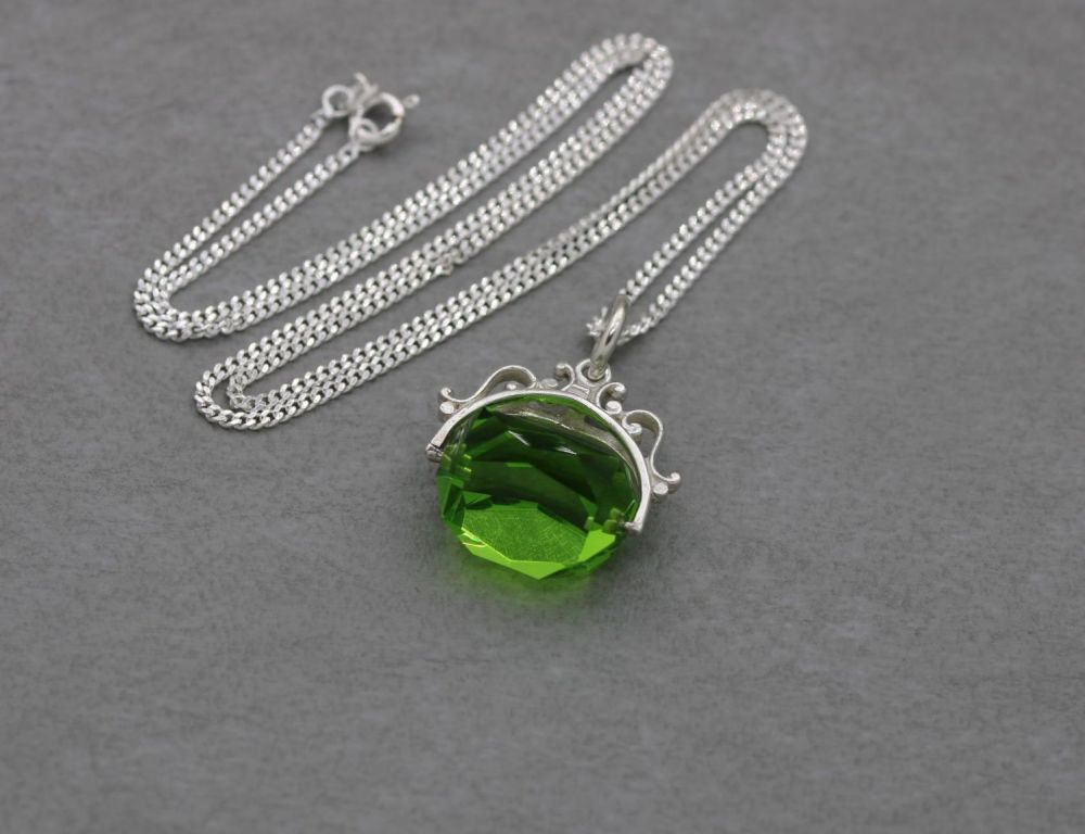 Modern sterling silver necklace with a faceted green glass spinning fob