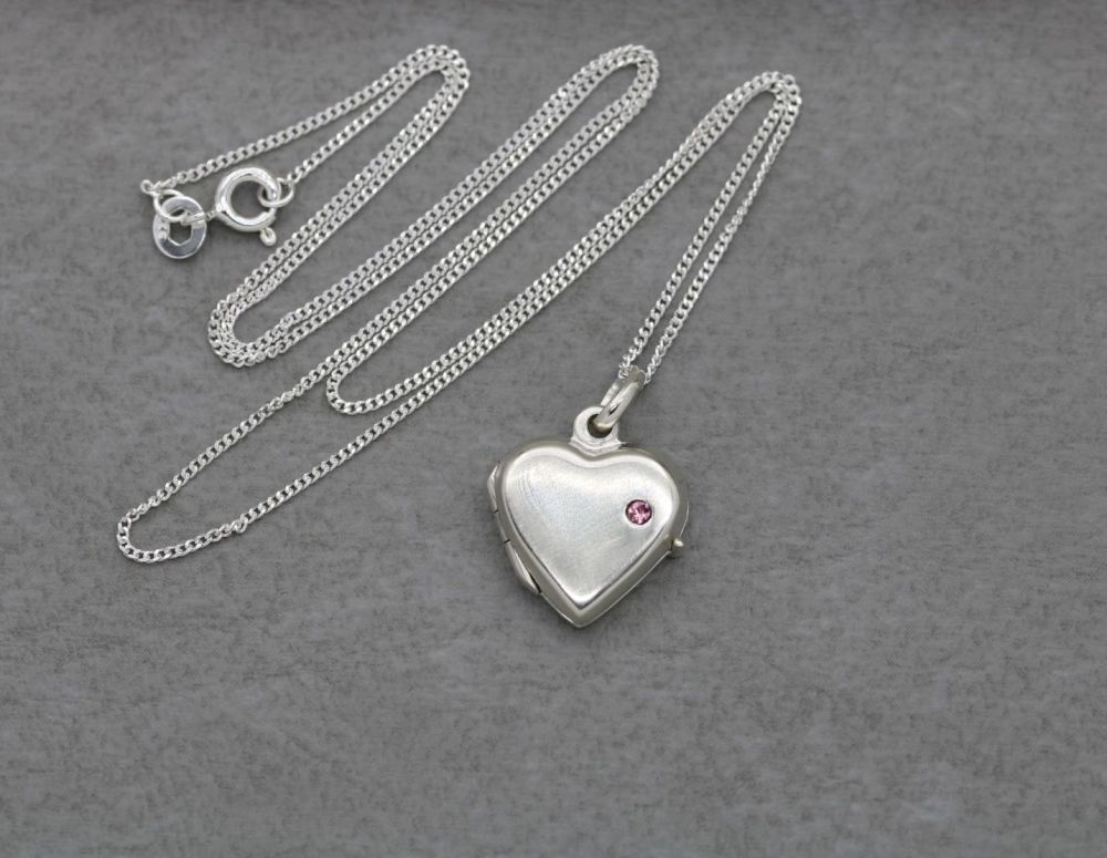 Small sterling silver heart locket set with a tiny pink stone