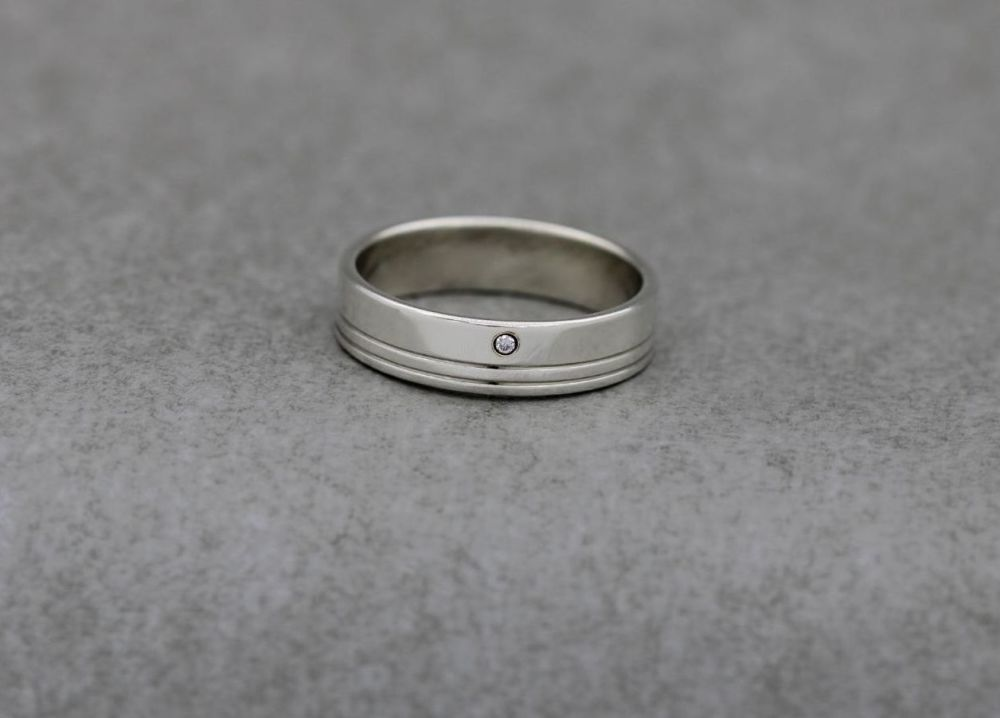 Sterling silver band ring with two stripes and a single clear stone
