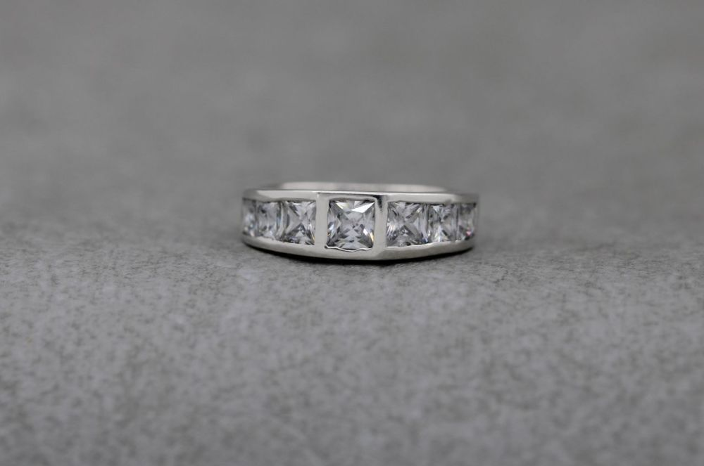 Gently graduated sterling silver ring with clear square stones