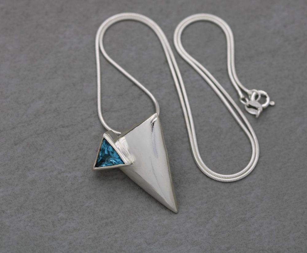 Handmade triangular sterling silver necklace with a faceted blue stone
