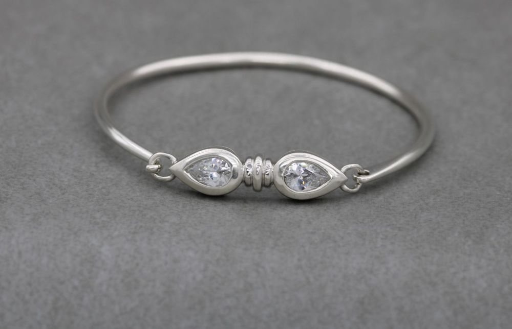 Sterling silver bangle with two clear faceted pear-cut stones