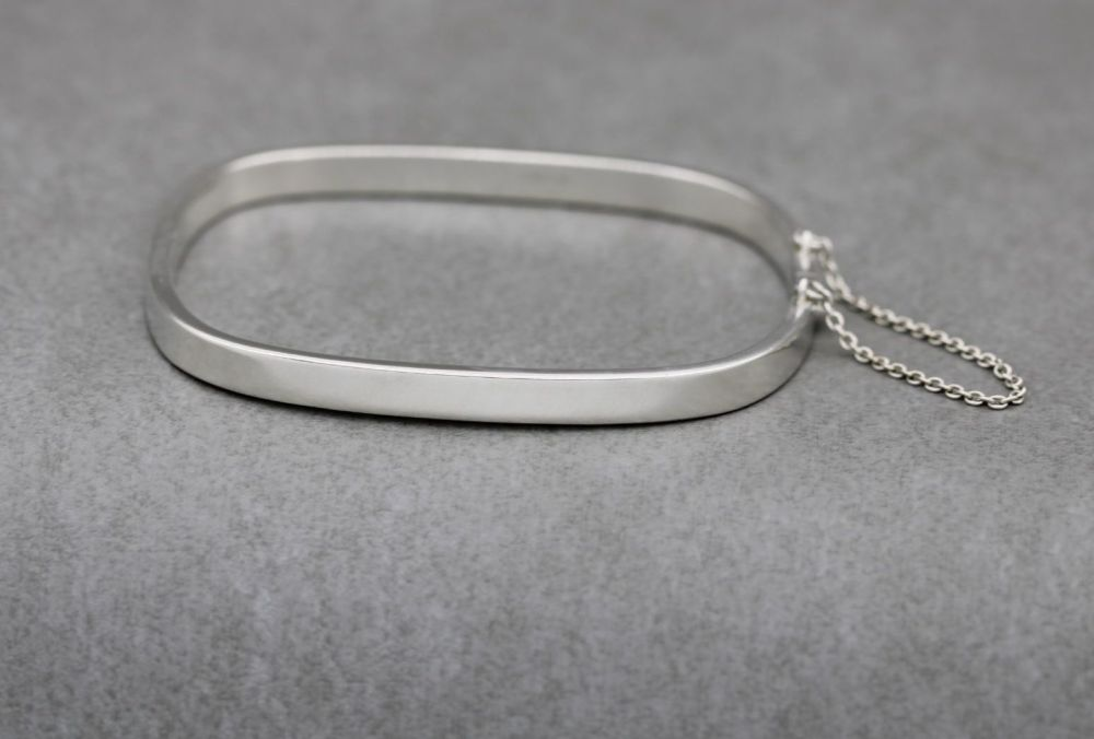 Rectangular sterling silver bangle with safety chain