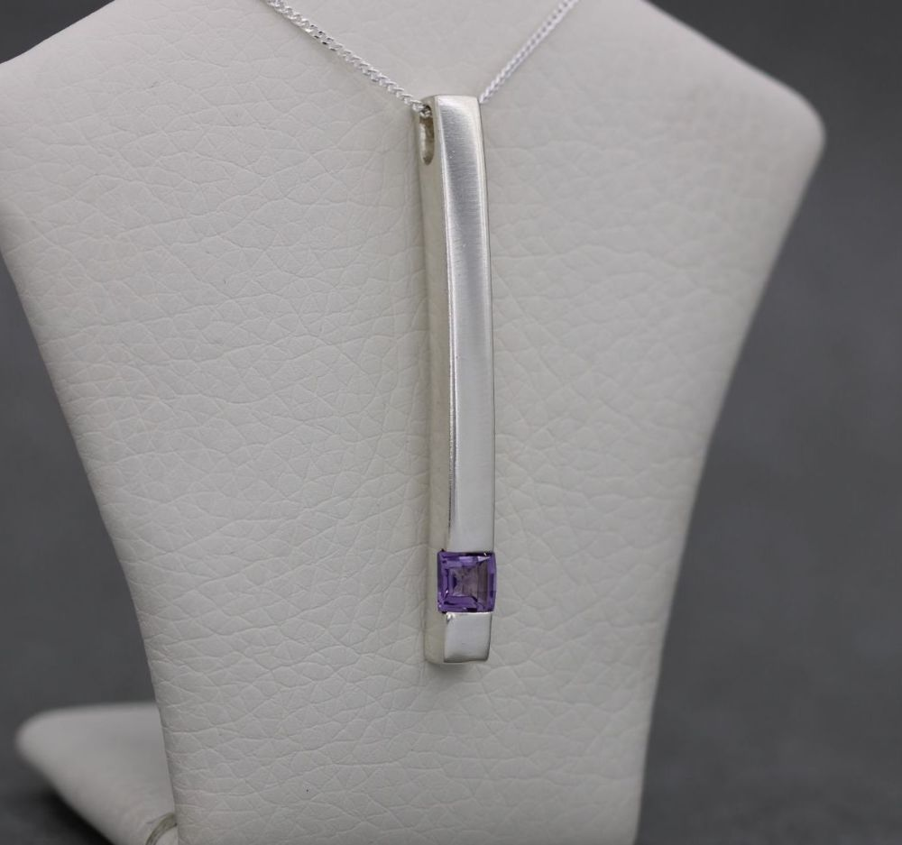 Sterling silver necklace with a long sleek amethyst set pendant