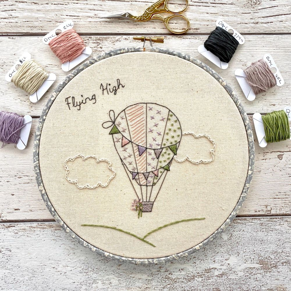 A photo of an embroidery hoop of a hot air balloon and the words flying high.  A selection of threads and a pair of scissors are laid around the hoop on a wooden background