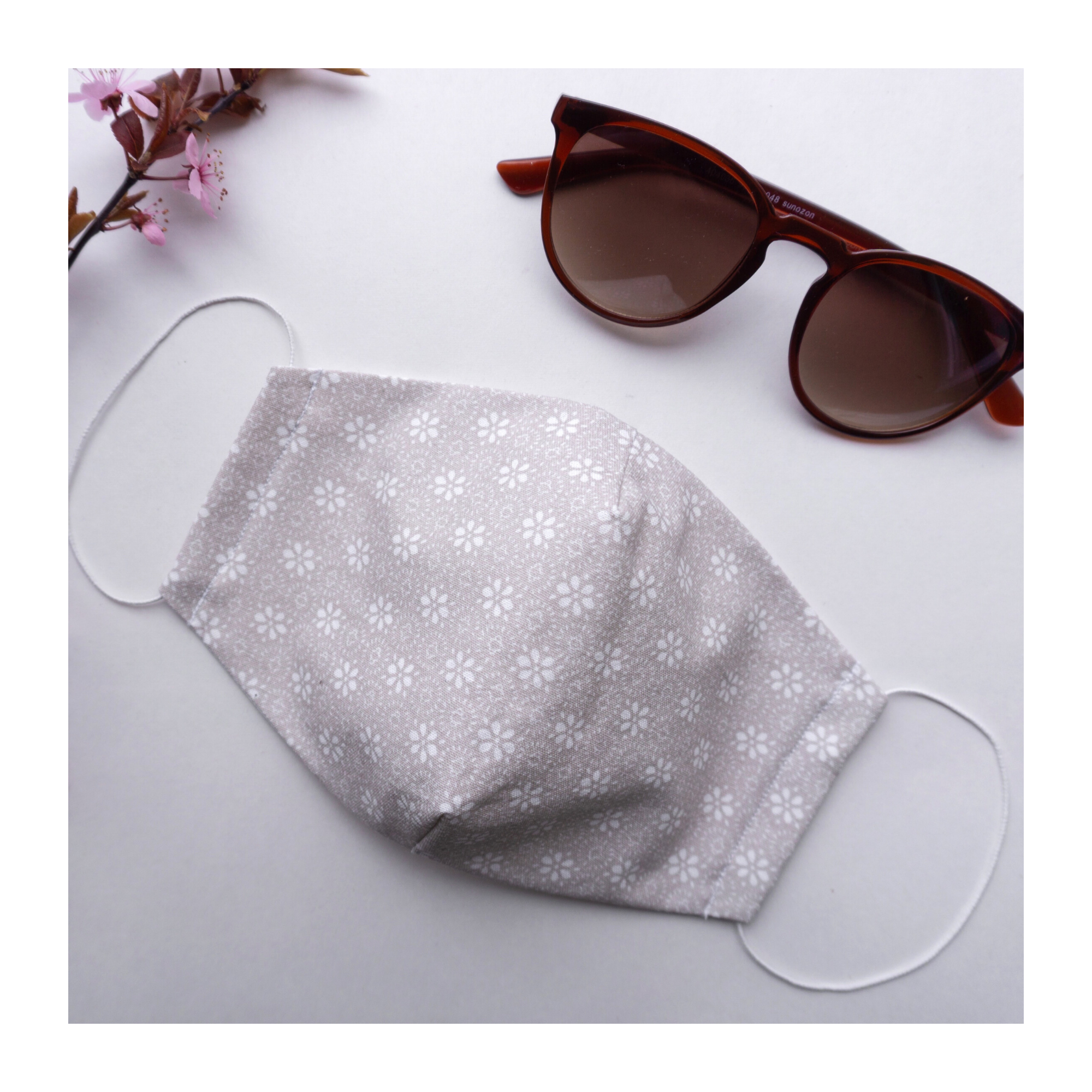 A fabric face mask lying next to a pair of sunglasses and pink flower