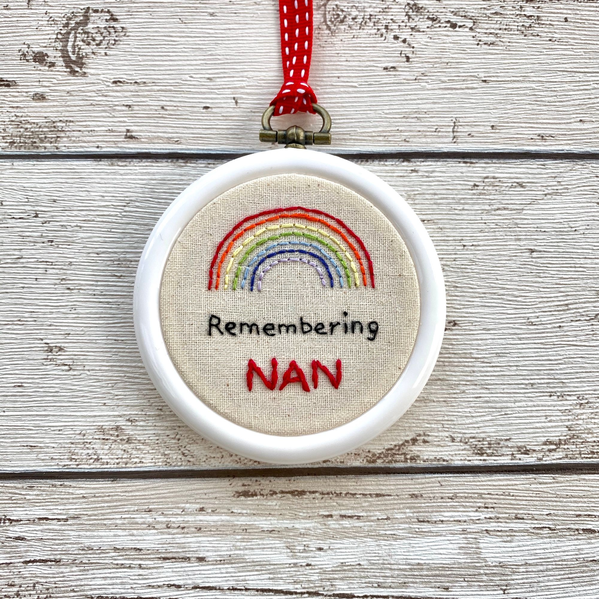 A white hoop with a stitched rainbow over the stitched words Remembering Nan.  Shown on a wooden surface.