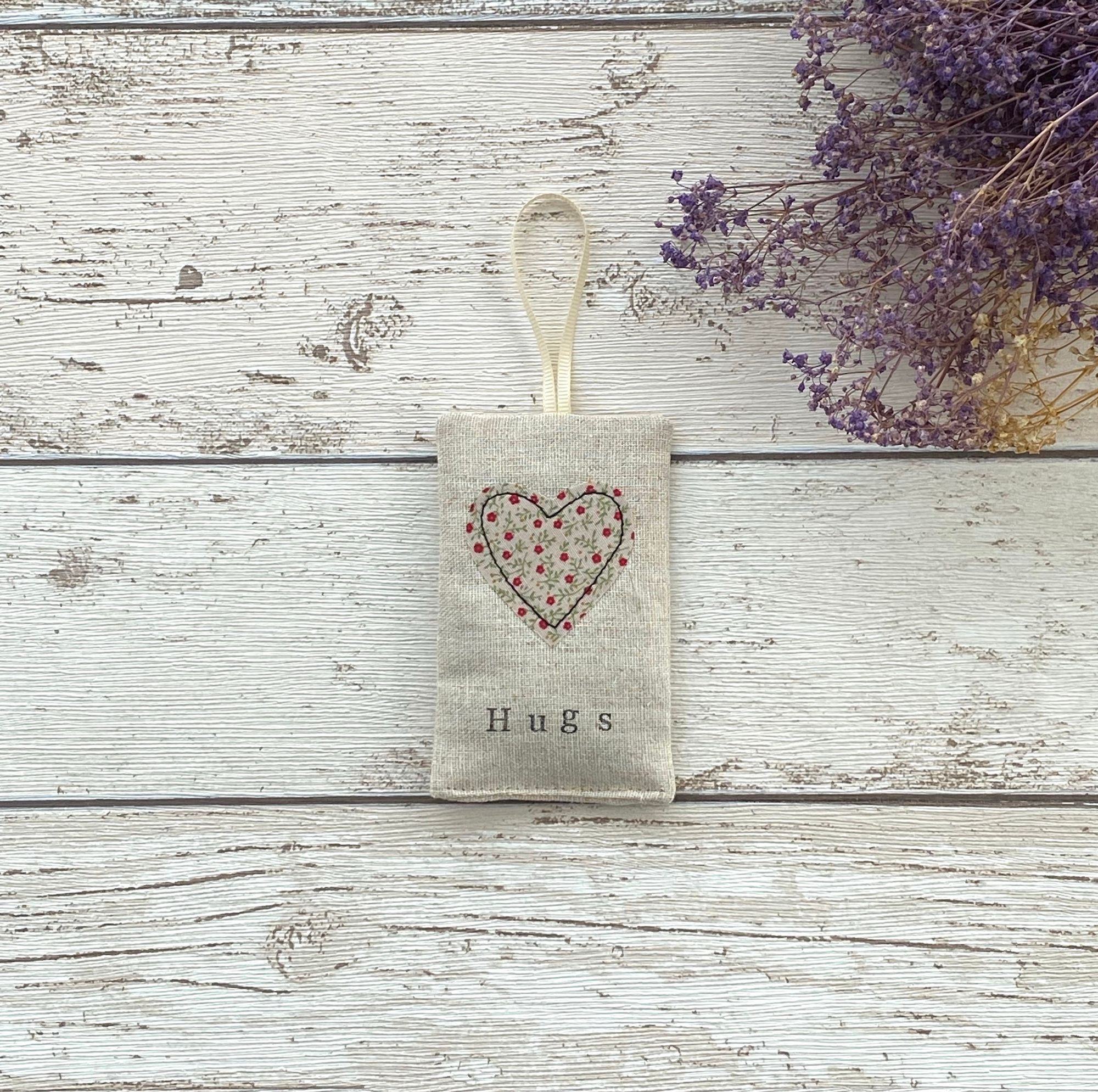 A rectangle linen bag with a fabric heart stitched to the front. The heart has little red flowers on. A cream ribbon is fixed at the top.  SHown on a wooden surface with purple dried flowers.