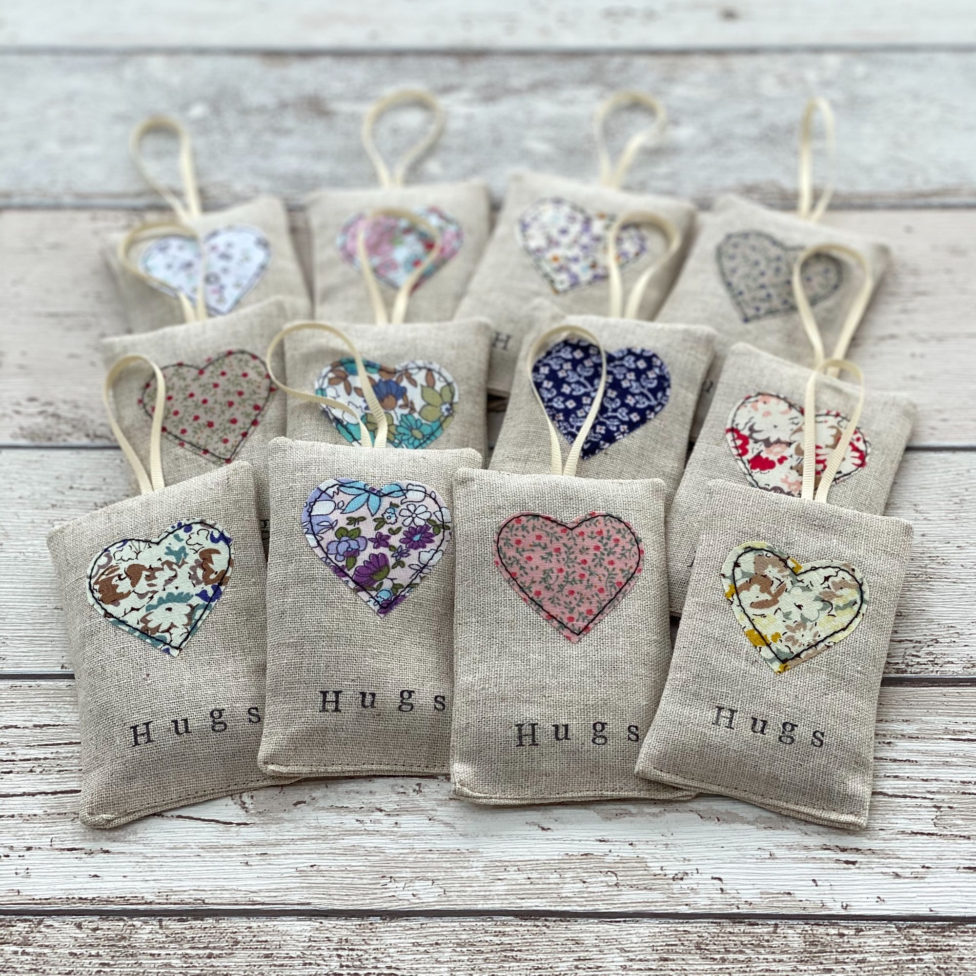A selection of linen lavender pouches with a fabric heart on the front and the word Hugs stamped with ink.  A  small ribbon attached at the top