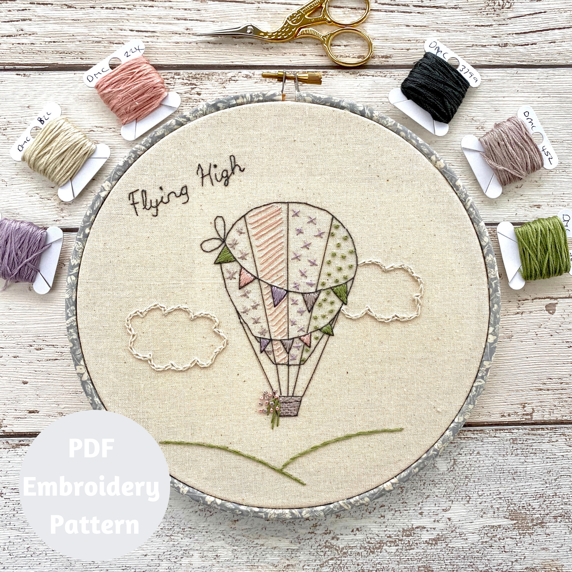 Hot air balloon hand embroidery pattern shown with coloured embroidery threads and embroidery scissors.