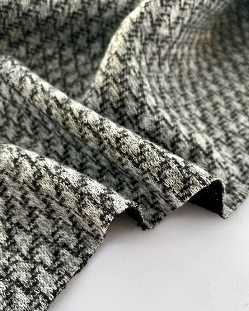 Black and grey textured woolly fabric laid on a white background and showing the edges in waves.  Photo by Just Sew Helen