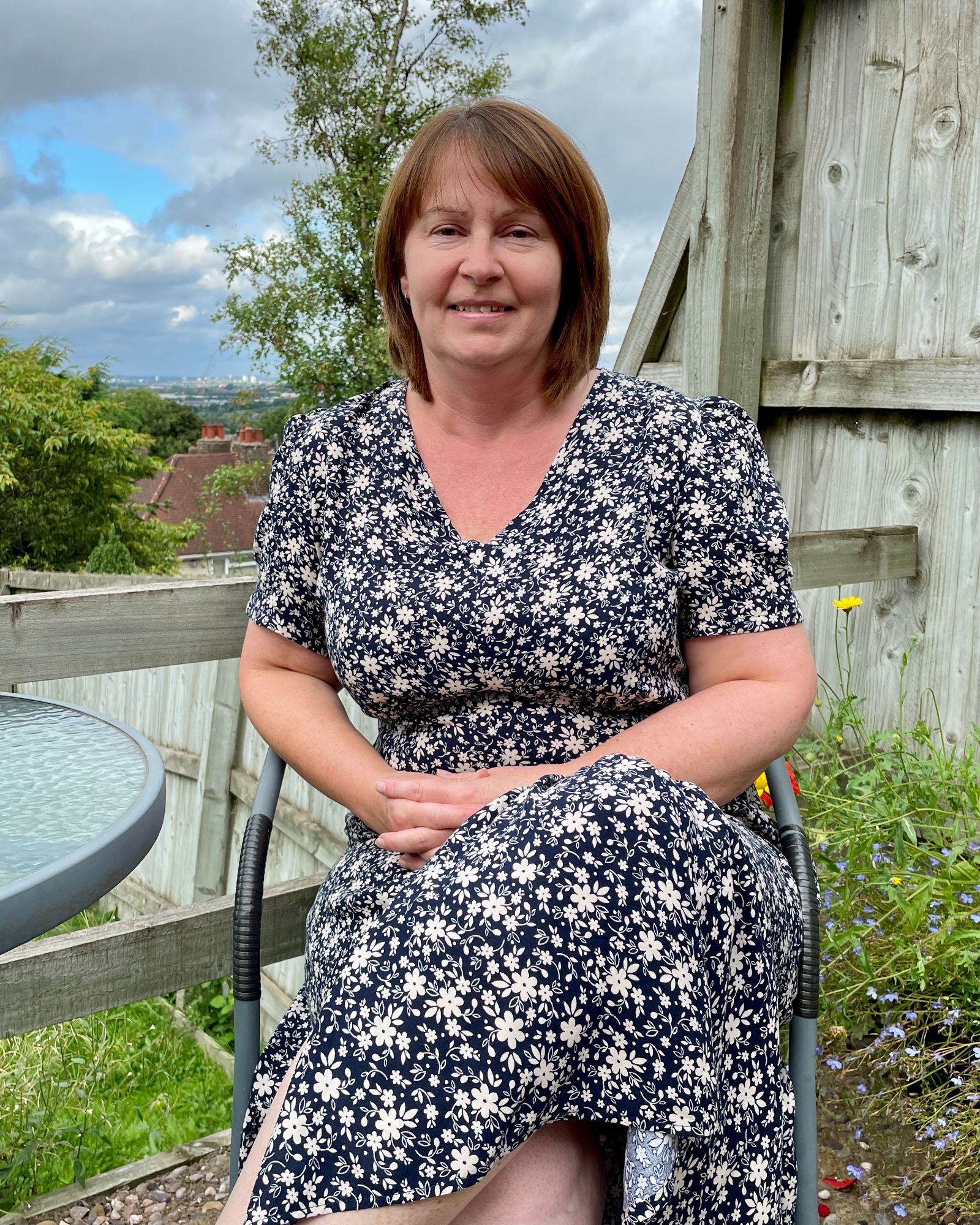 A lady sitting in the garden wearing a navy flowered summer, v neck dress