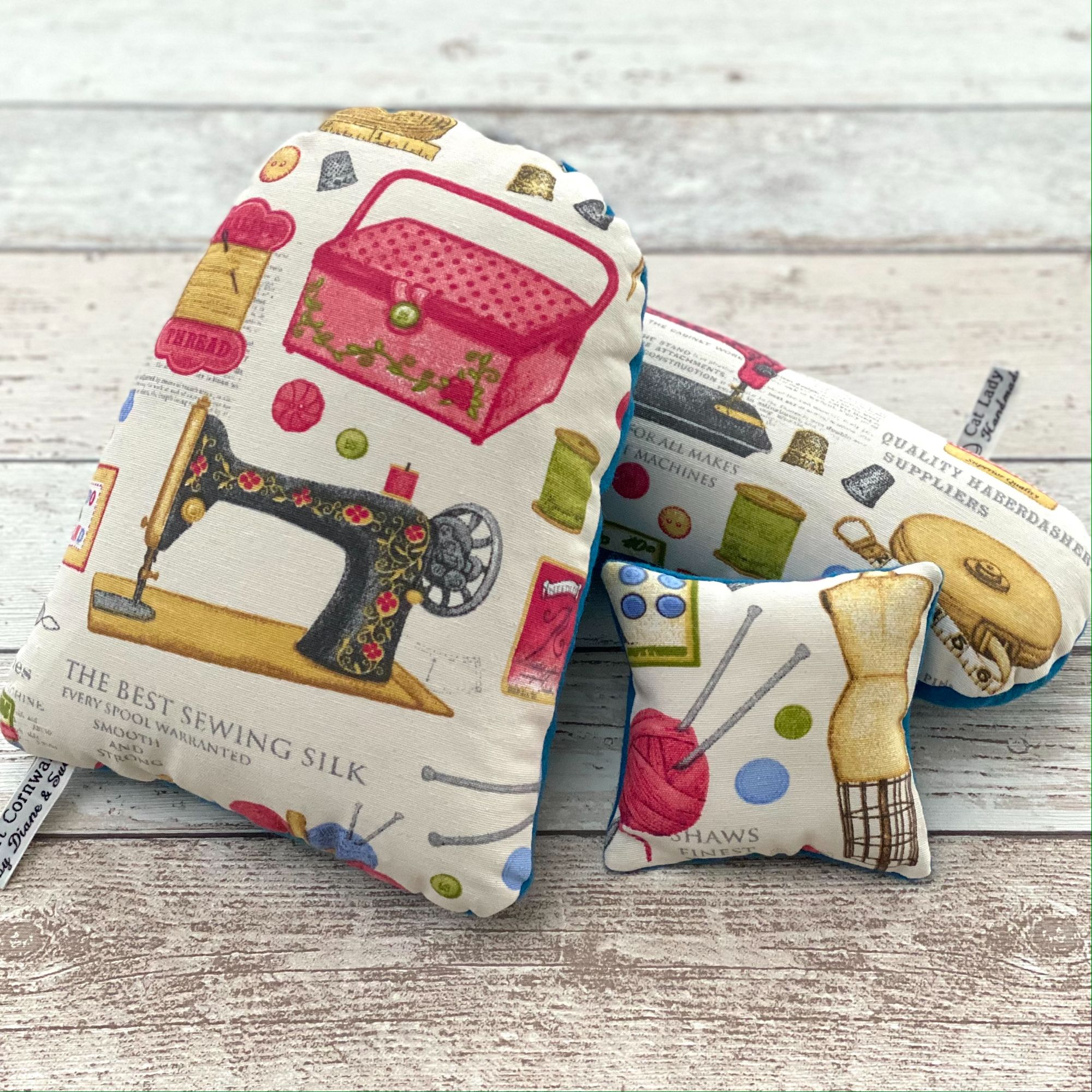 Three handmade sewing aids , a ham, a sleeve press and a pin cushion made with sewing themed fabric.