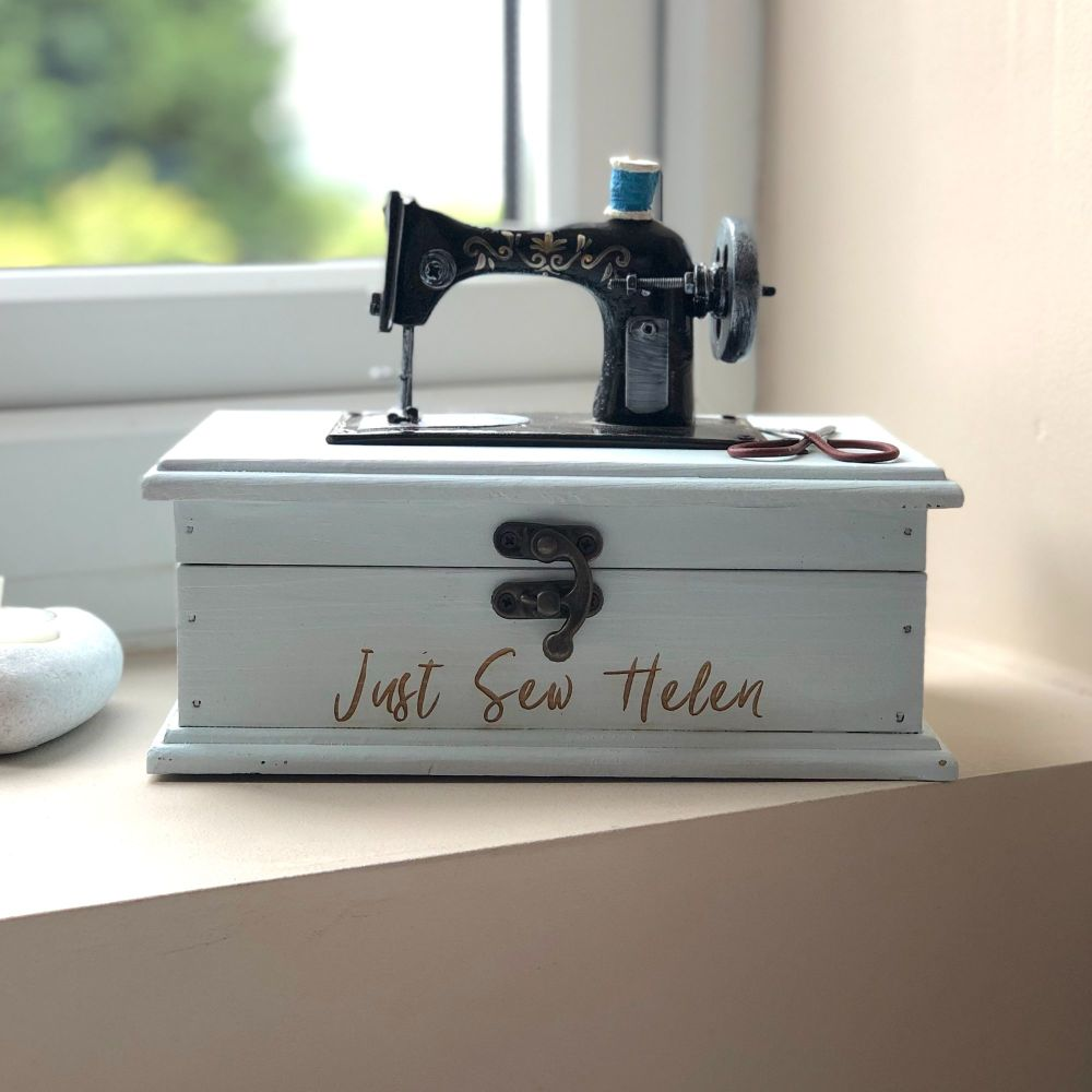 A pale blue wooden box with a front catch and a model sewing machine on the top.  The words Just Sew Helen are burnt onto the front of the box