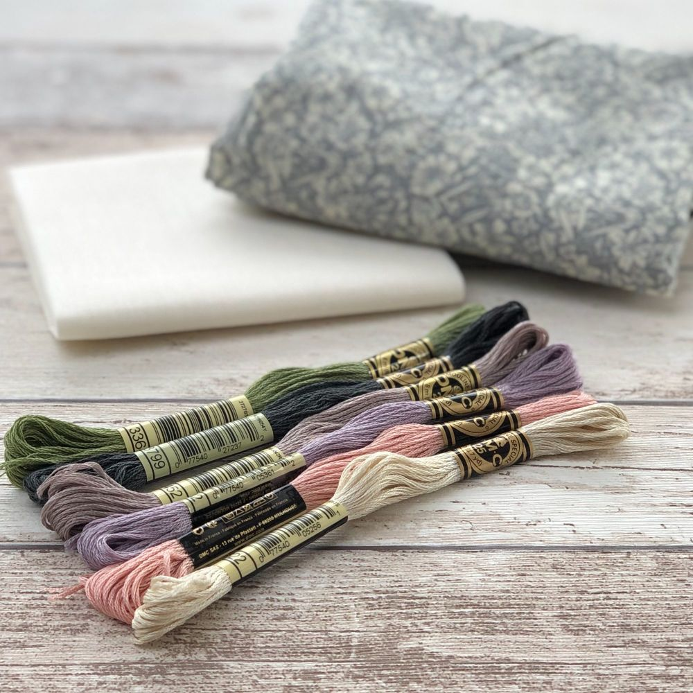 Six embroidery Threads and two fabrics, a grey floral and natural cotton placed on a wooden background