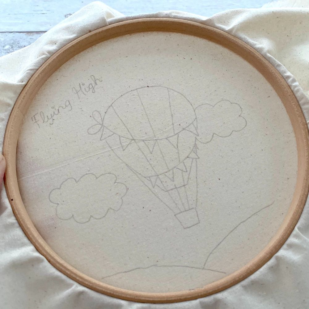 A wooden embroidery hoop and natural cotton fabric inside with a hot air balloon drawn on in pencil.