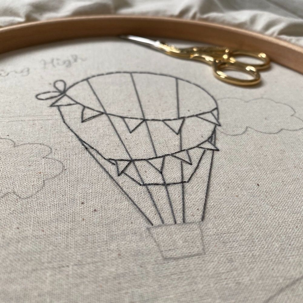 A work in progress embroidery hoop showing outline stitching of a hot air balloon picture in black thread, a small pair of scissors are lying towards the edge of the hoop.