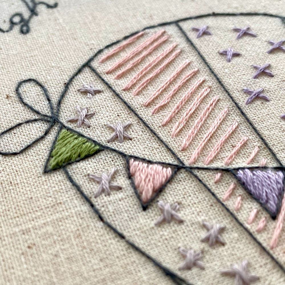 Hand embroidered balloon with stars and long stitches in pink and purple threads