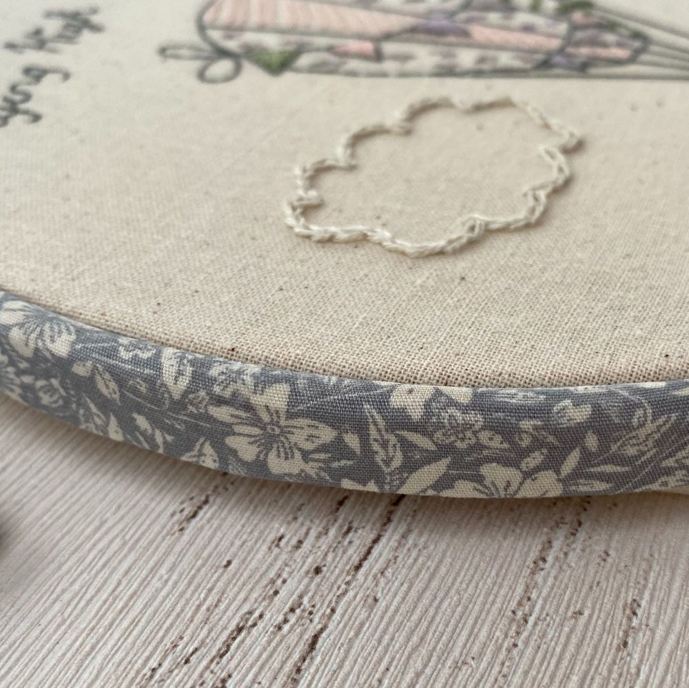 The edge of an embroidery hoop covered with grey floral fabric