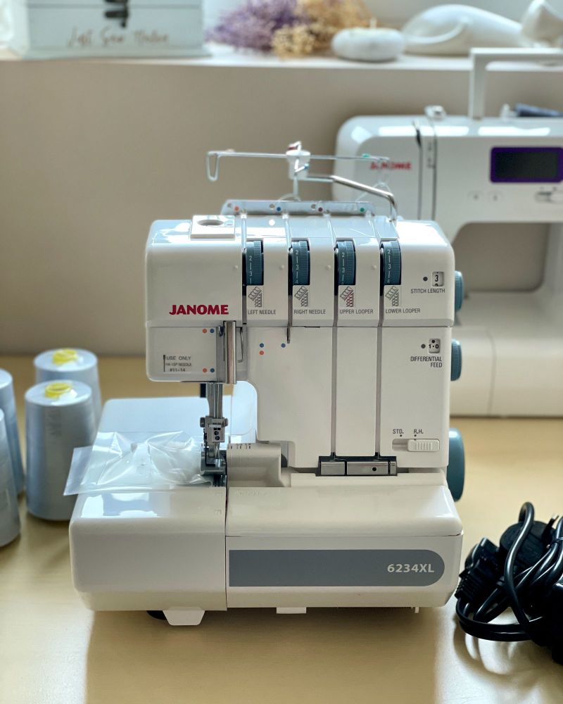 A Janome Overlocker 6234XL machine on a desk with spools of cotton. There is another Janome sewing machine behind it, below a window sill.